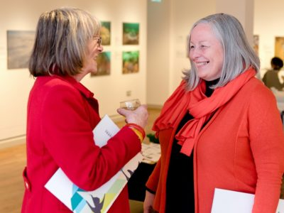 Two ladies talk in a gallery private view