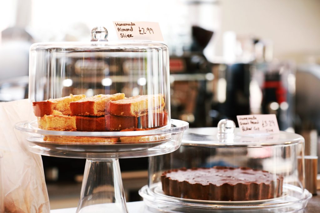 cakes under bell domes on display in a cafe