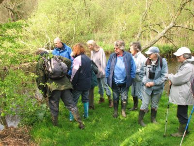 A group of older volunteers by a river and trees in walking gear