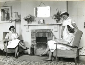 Old photo of three nurses in a living room, talking and relaxing