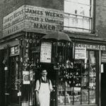 Black and white photo of man standing in front of jewellers shop