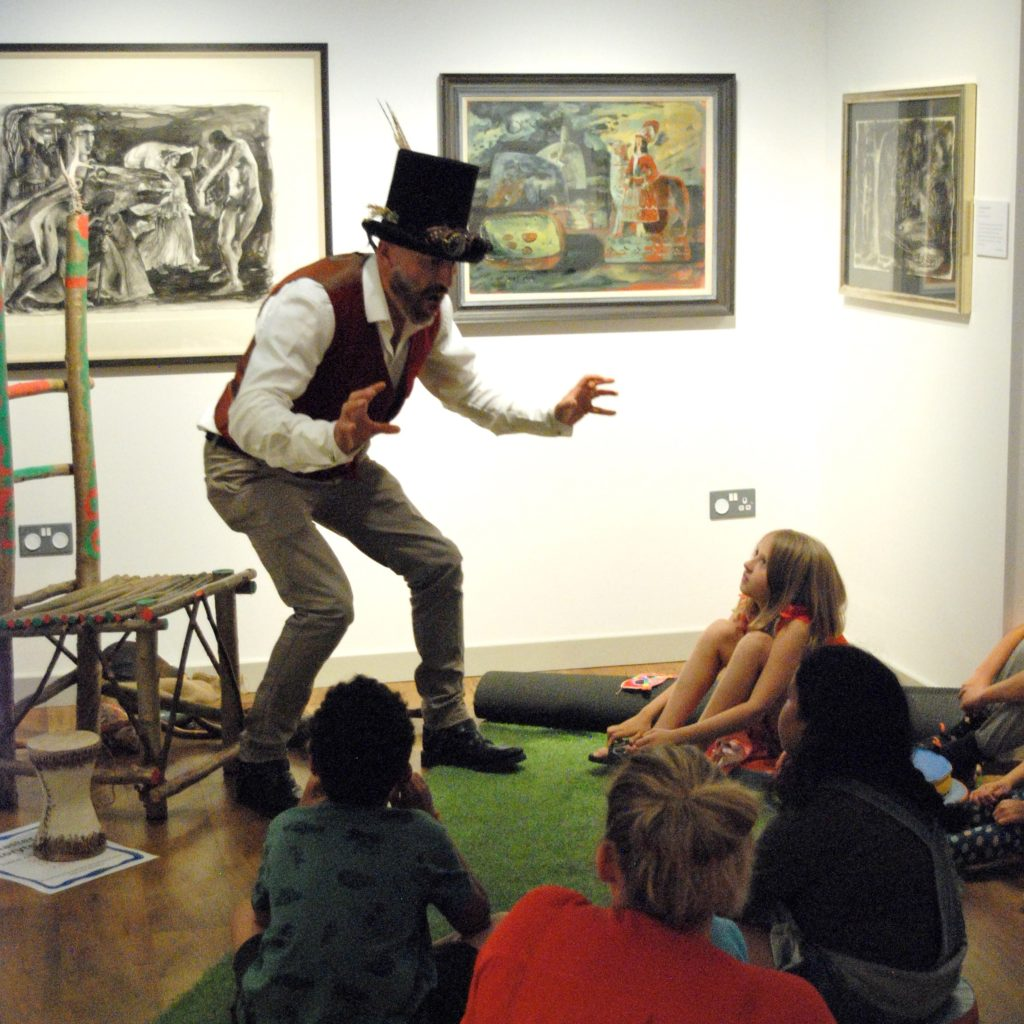 A man in a top hat poses to entertain children in a gallery