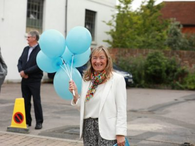 A lady holding a bunch of blue balloons