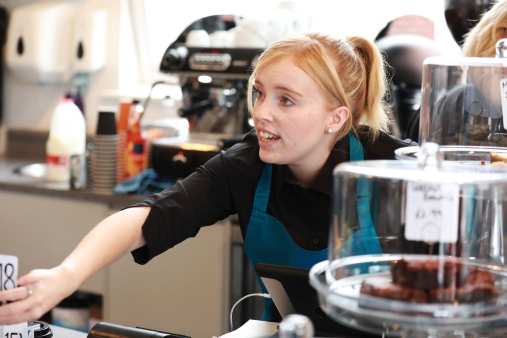 young adult waitress in green apron leans over coffee counter