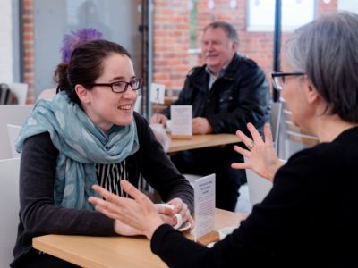 Two women sit at a table in a cafe having a happy conversation