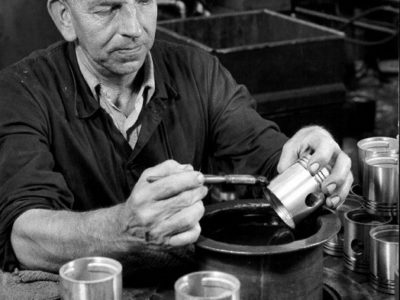 Photograph of a man in simple cloths at a workbench, working on a piston