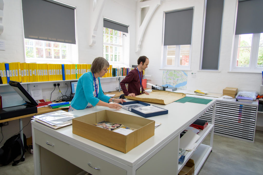 Photograph of two people working with documents in the King Research Room.